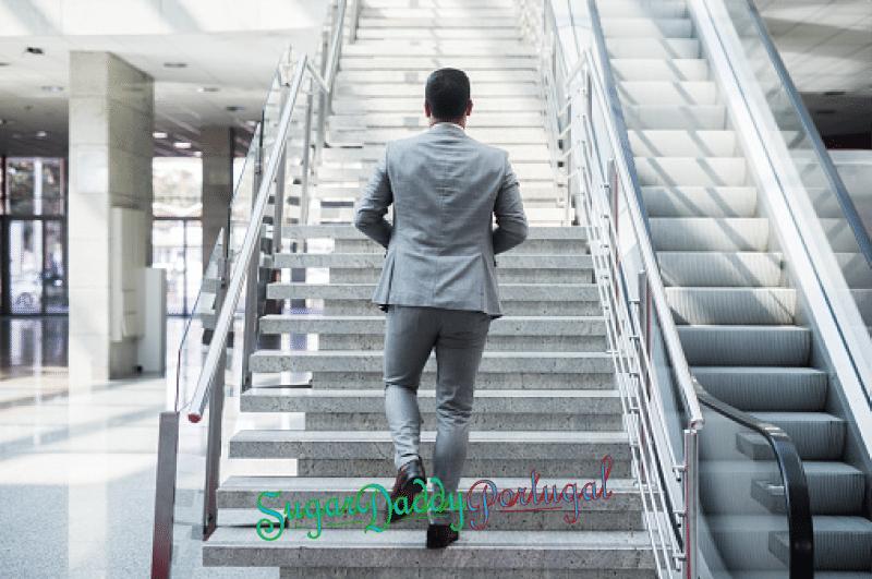 esplénda hombre en traje de negocios sube escaleras
