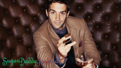Hombre sonriente en un sillón de cuero con un vaso de whisky y una tarjeta de crédito.